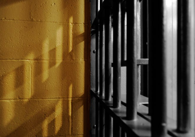 Shadows on a wall of a jail cell from the barred door