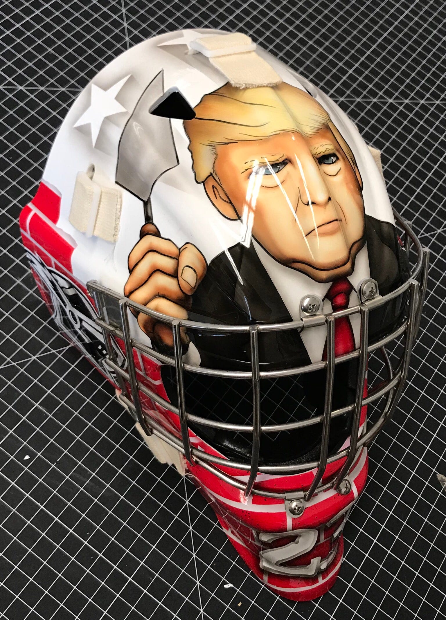 Youth hockey goalie's mask features Donald Trump in brick wall theme