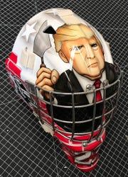 A goalie mask featuring Donald Trump.