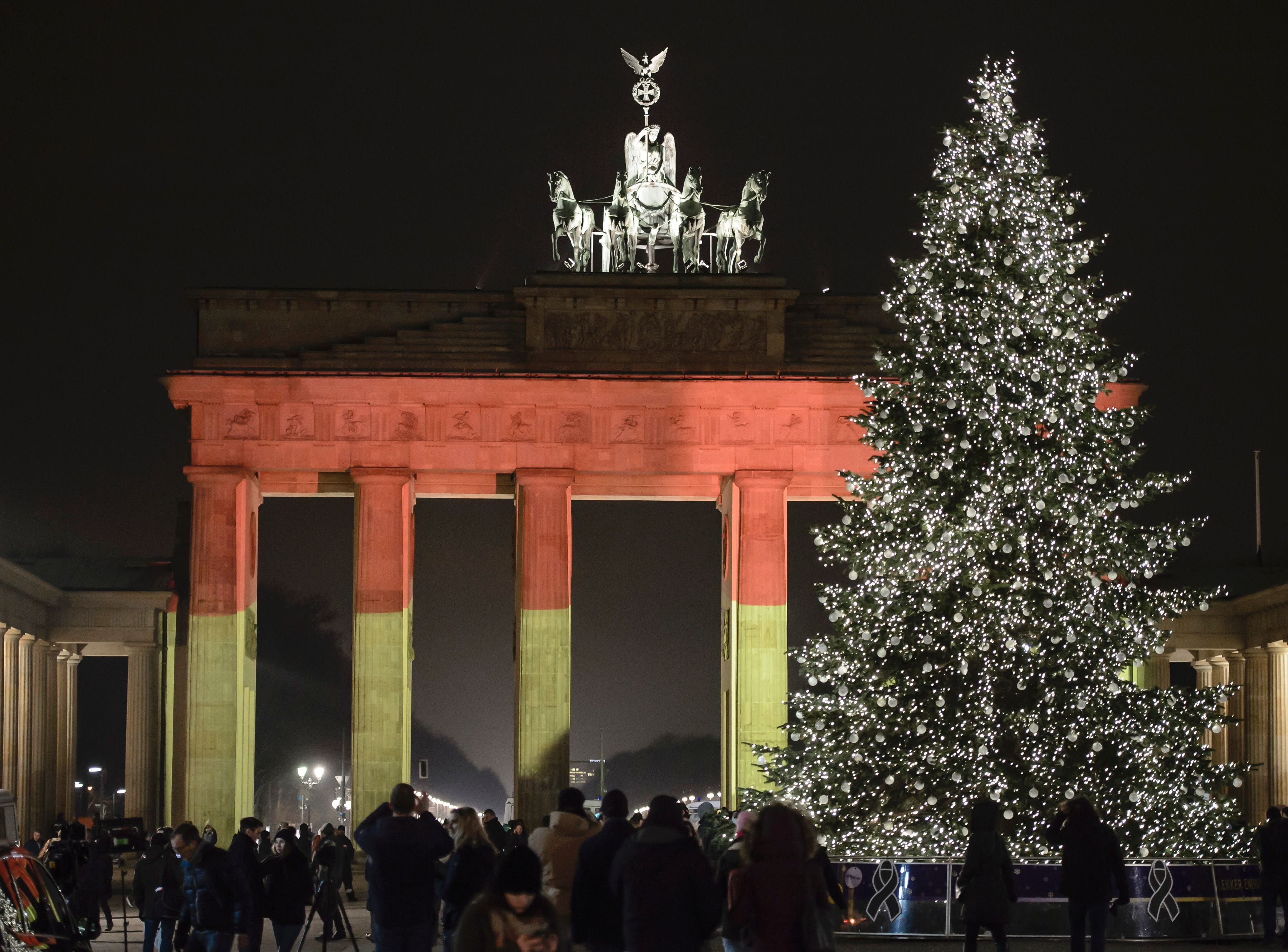 """The Brandenburg Gate is seen in the colors of the German flag in Berlin on December 20, 2016 one day after a truck crashed into a Christmas market. German police said they were treating as """"a probable terrorist attack"""" the killing of 12 people when the speeding lorry cut a bloody swath through the packed Berlin Christmas market. / AFP PHOTO / CLEMENS BILANCLEMENS BILAN/AFP/Getty Images ORG XMIT: 36 ORIG FILE ID: AFP_JA9DT"""