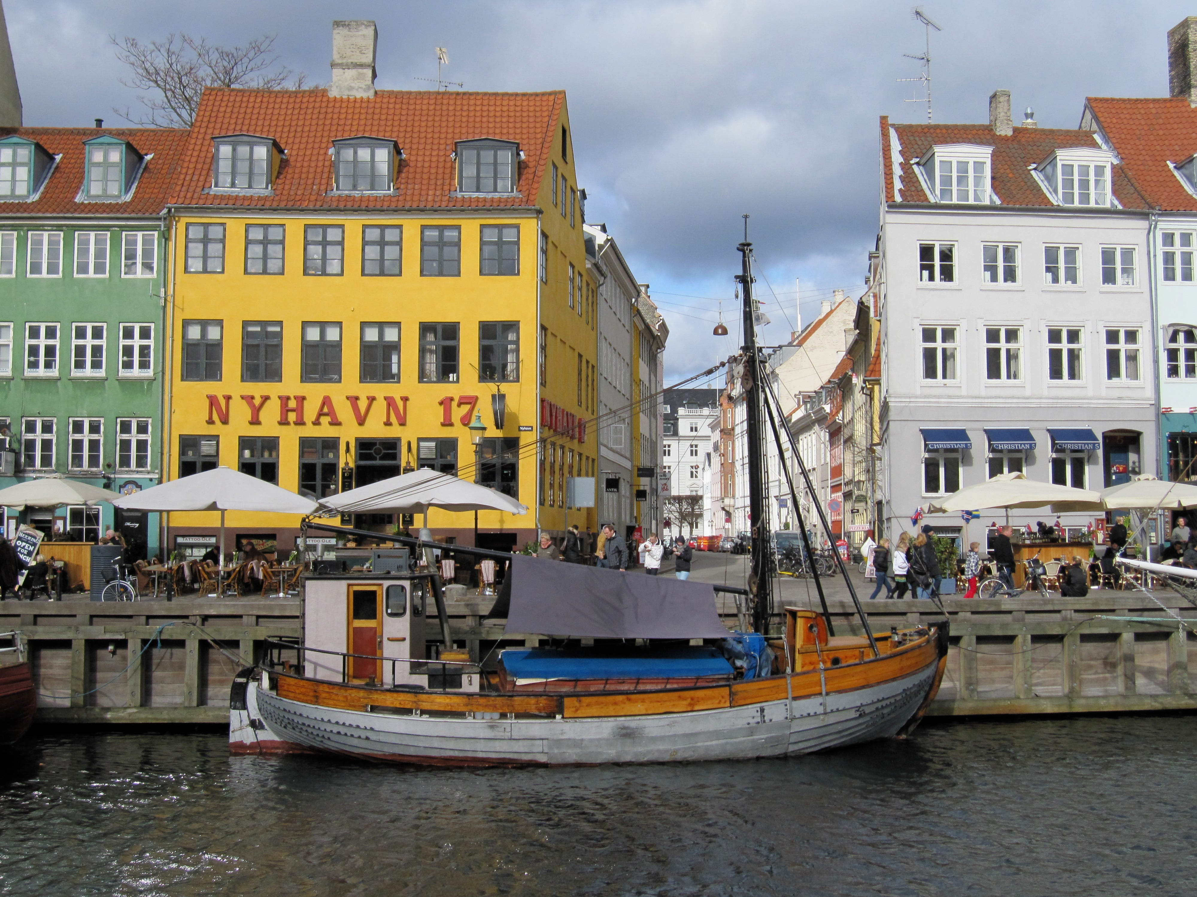 """Travel -- Copenhagen -- The historic port area of Nyhavn, now a tourist mecca filled with restaurants and sidewalk cafes.-- HAPPYDANES: Danish people are the happiest people in the world, several studies say, due to their quality of life, a government that offers good medical care and vacations and even pays students to stay in high school, strong family ties and an enjoyment of life. Probably good genes help, too. We visit Copenhagen, a picturesque and compact city whose residents also are so eco-conscious that a third bike to work. Amid buildings dating back to medieval times and the historic port of Nyhavn, now filled with outdoor cafes, we meet smiling and helpful Danes and even participate in a program open to anyone called """"Dine with the Danes."""" Yes, the family, including a charming high schooler, seemed happy as they served mountains of fish – smoked, pickled, fried – washed down with schnapps, beer and wine. Y (Via MerlinFTP Drop)"""
