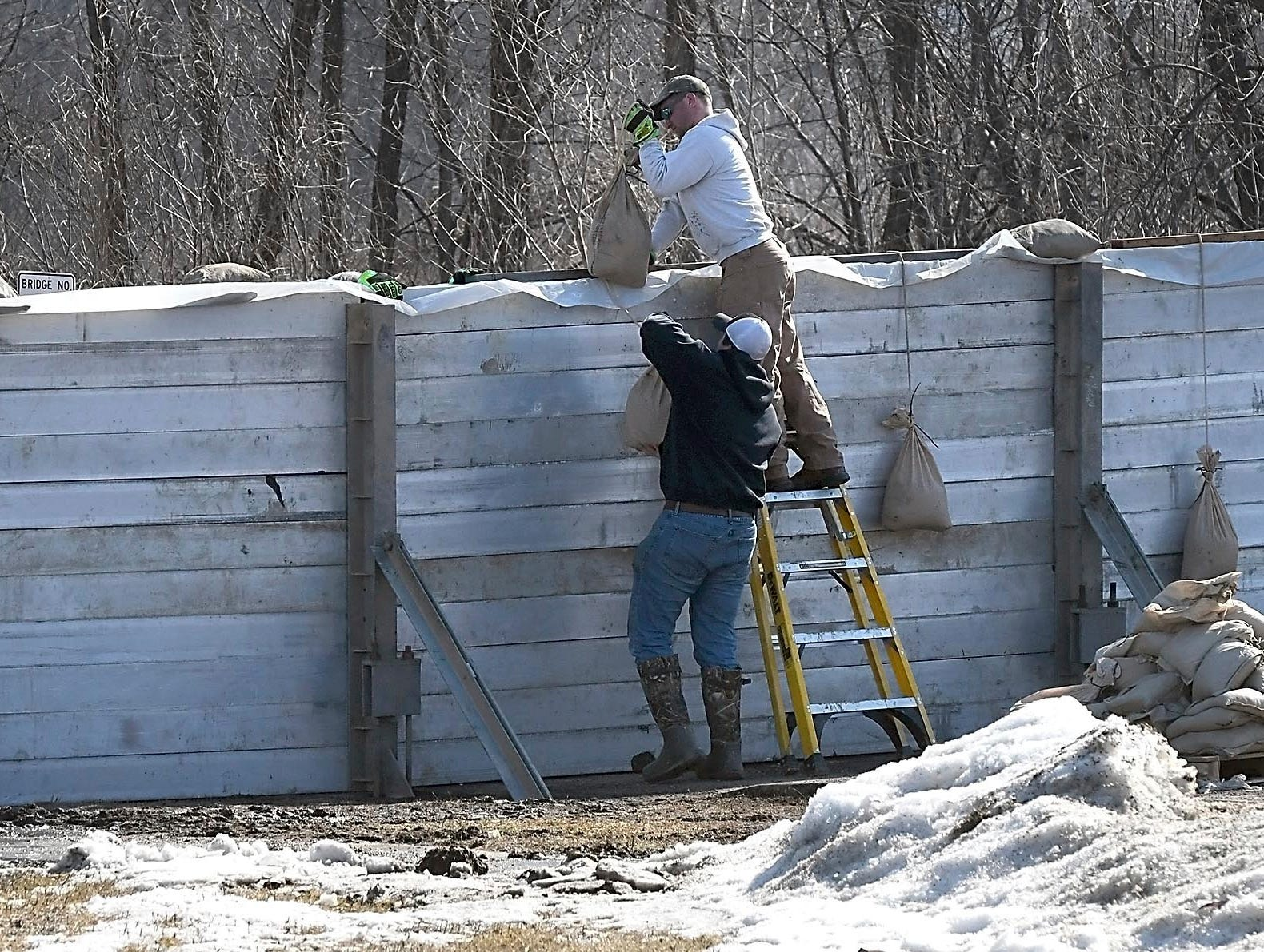 Henderson firefighters put the finishing touches on a floodwall across Highway 19 Wednesday, March 20, 2019, in Henderson, Minn.