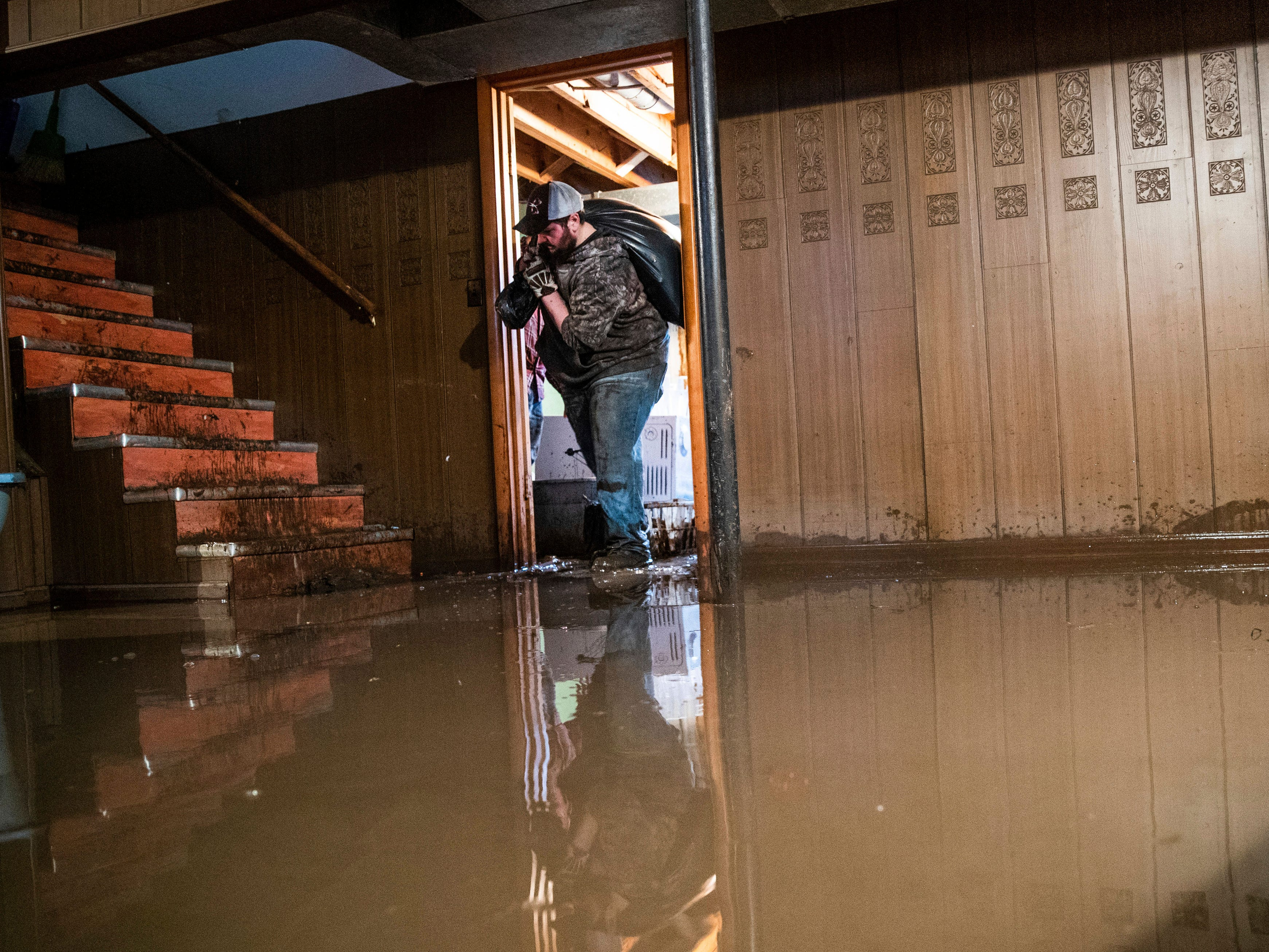 Jake Nebuda removes damaged items from the basement of home on March 19, 2019, in North Bend, Neb. The home had over 40 inches of water in it earlier this week.