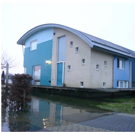 "A floating home in Maasbommel, The Netherlands. The house is built on concrete hulls and anchored to mooring posts. The houses rise and fall as the river level rises. The development, called ""Room for the River,"" includes 26 homes."