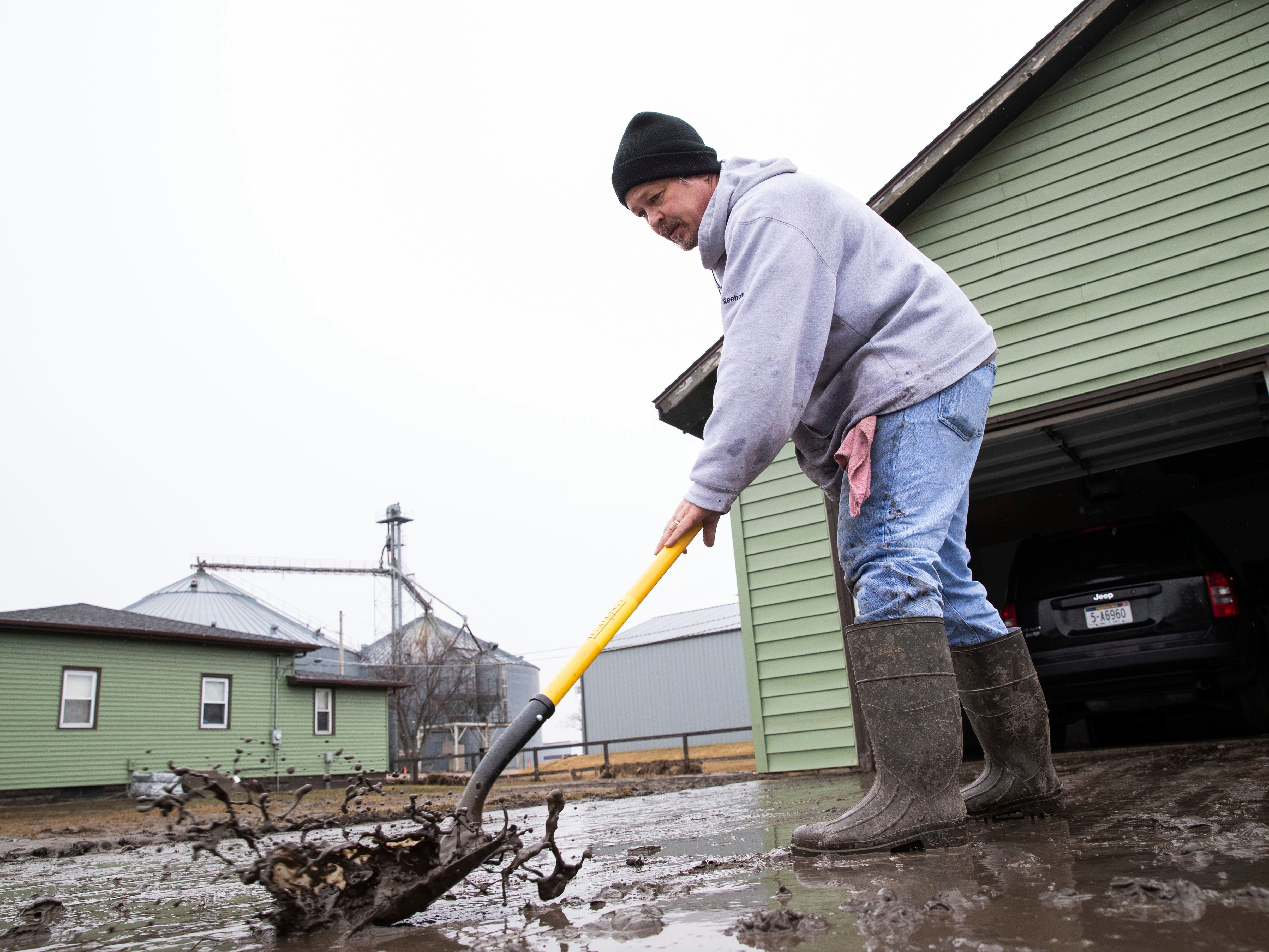 Mike Loeffler clears mud from his driveway while dealing with the aftermath of major flooding on March 19, 2019, in North Bend, Neb.  The president of the Nebraska Farm Bureau says farm and ranch losses due to the devastating flooding could reach $1 billion in the state.