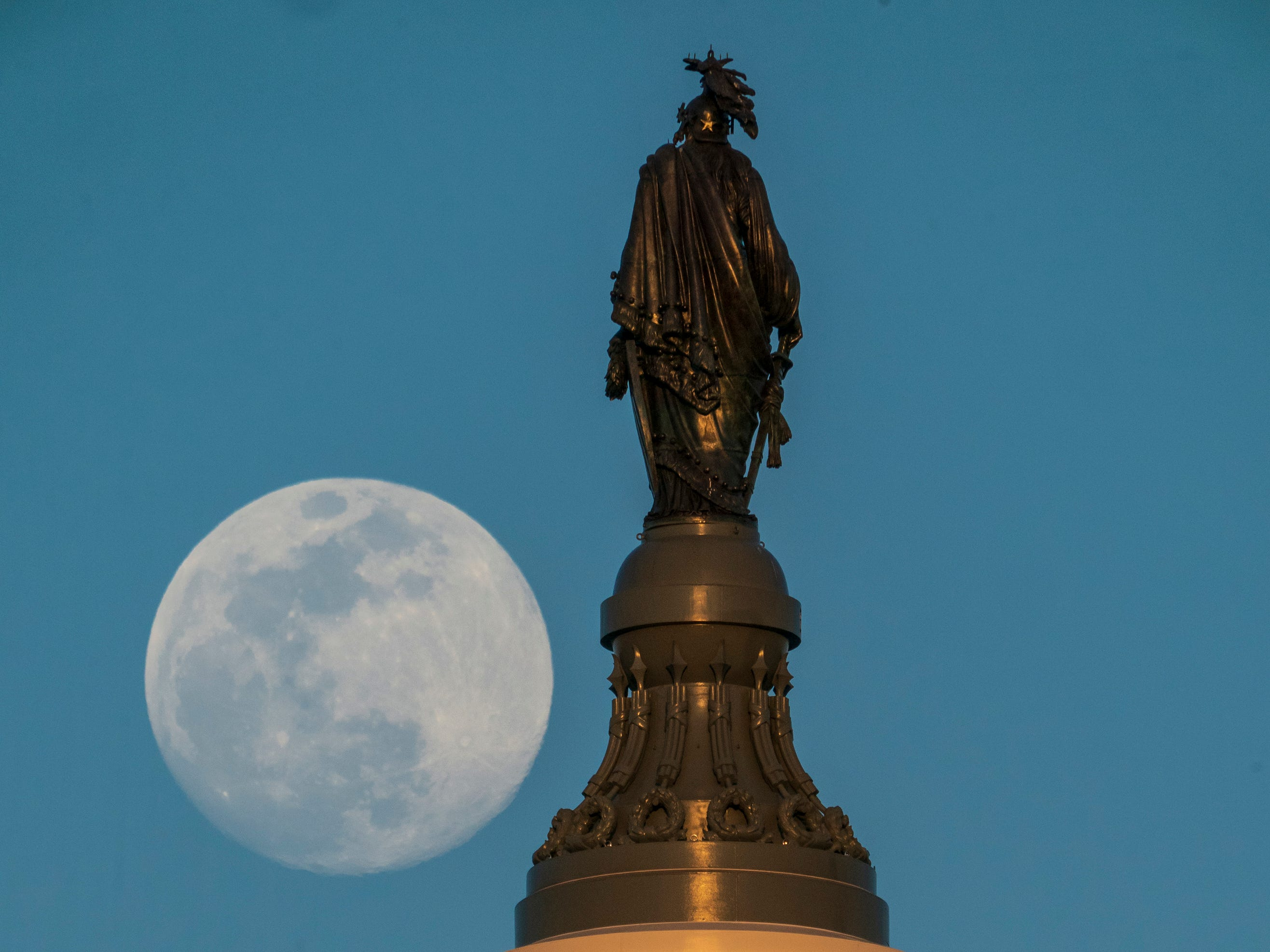 A full moon rises behind the Statue of Freedom atop the U.S. Capitol in Washington, Tuesday evening, March 19, 2019.