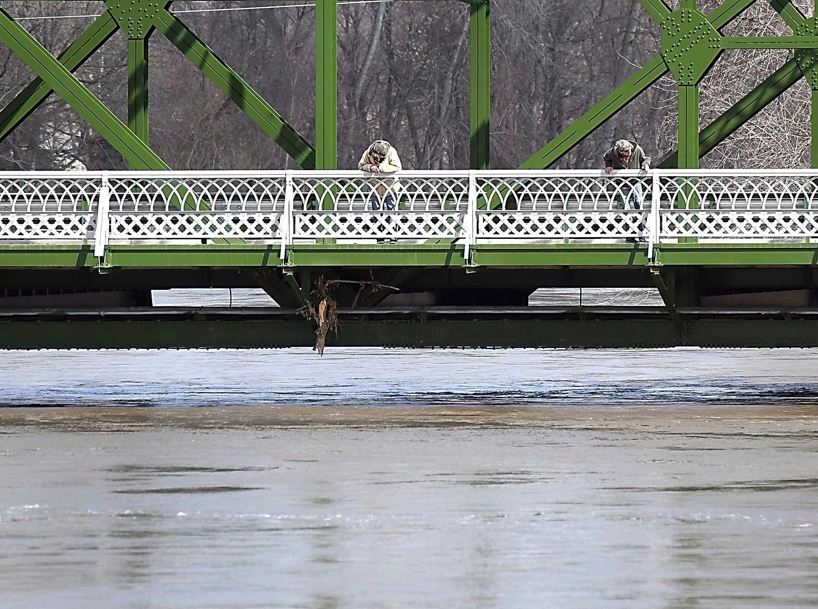 Two men look at a raging Minnesota River beneath the Highway 99 bridge Wednesday, March 20, 2019 in St. Peter. High water is threatening to close the bridge.