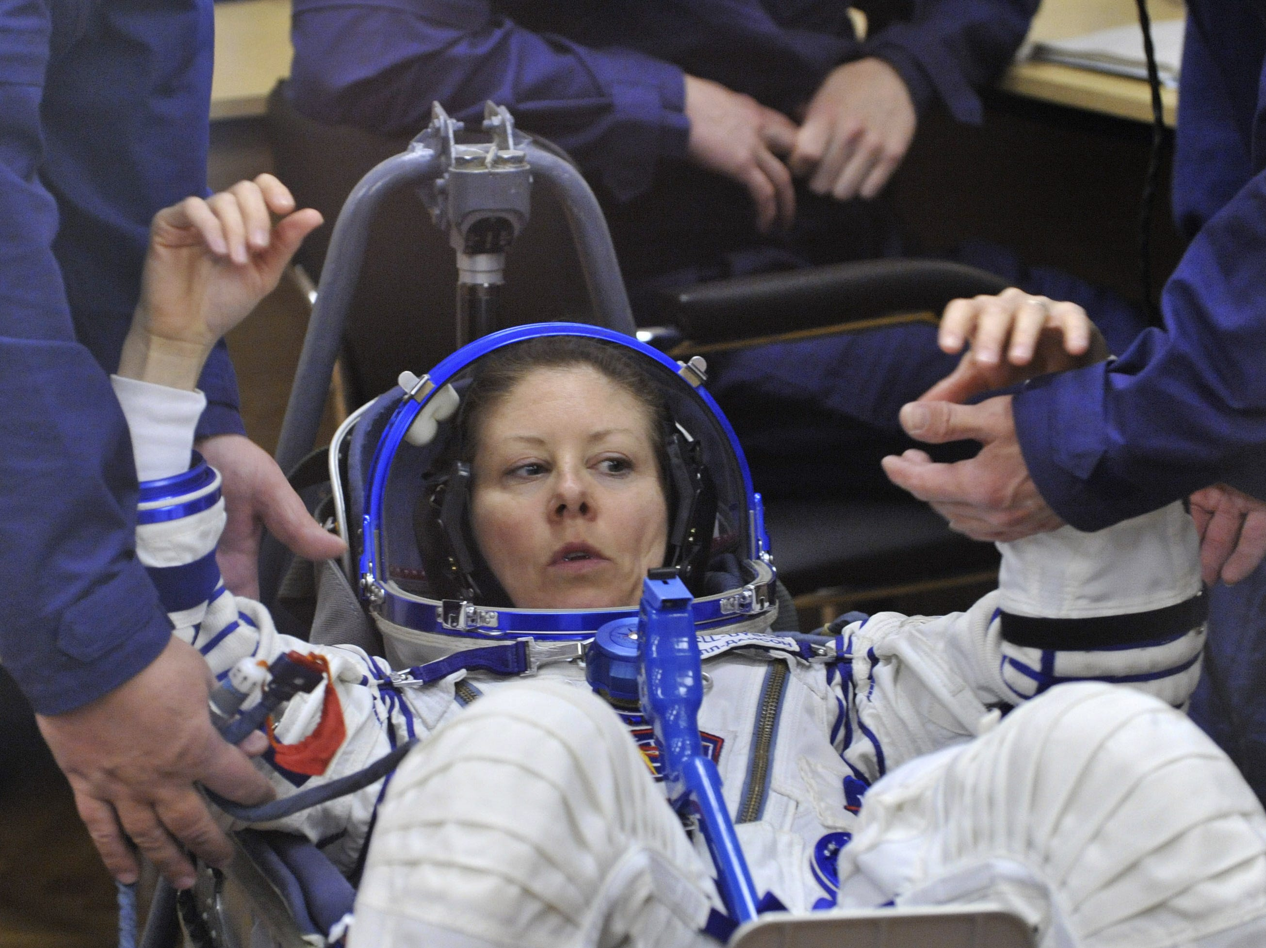 Astronaut Tracy Caldwell Dyson gets put into her space suit at Kazakhstan's Russian-leased Baikonur cosmodrome on April 2, 2010.
