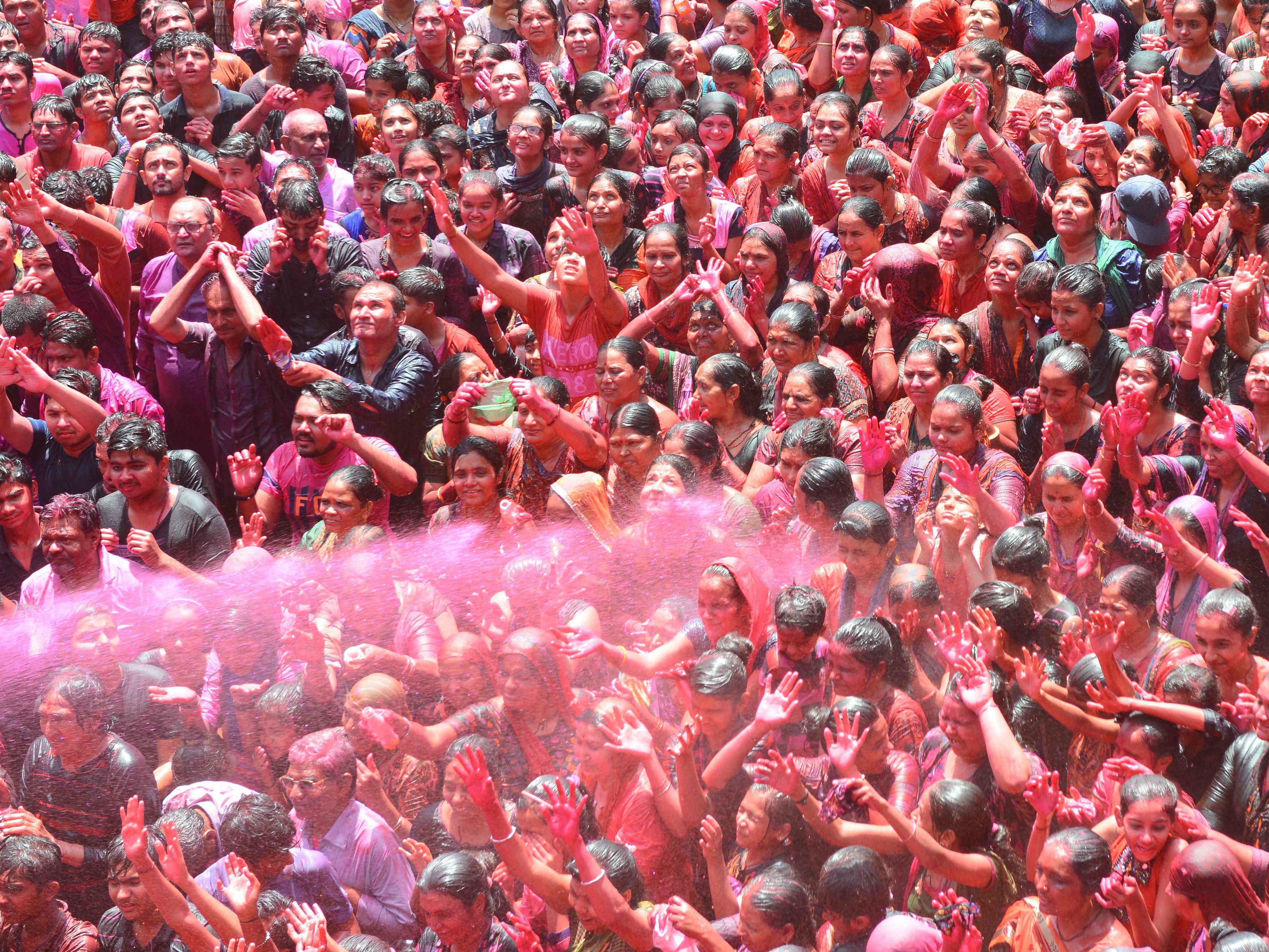 Indian Hindu devotees are sprayed with colored water as they celebrate the Holi festival at the Kalupur Swaminarayan Temple, in Ahmedabad on March 20, 2019.