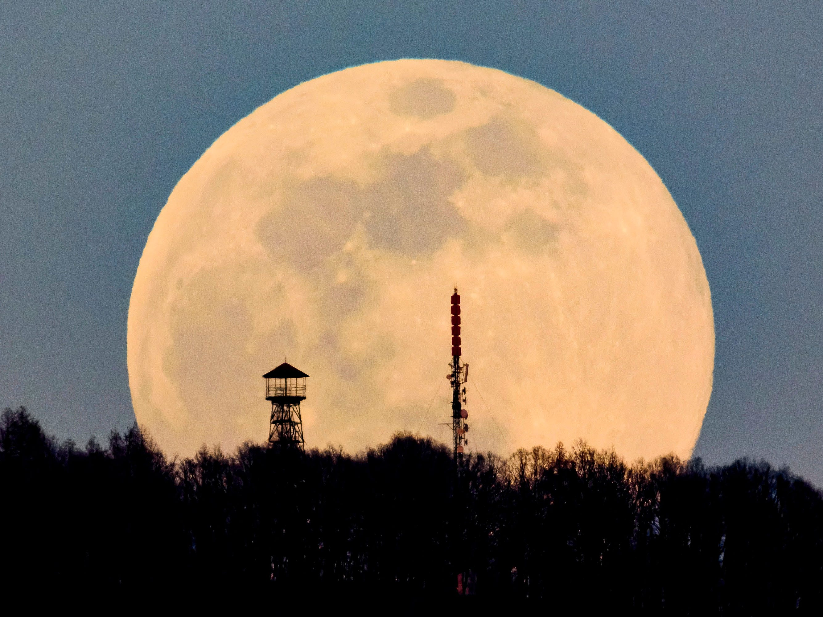 A lookout tower, left, and the broadcast tower of Antenna Hungaria at the top of Karancs mountain are backdropped by the rising moon as seen from the vicinity of Karancskeszi village, northeast of Budapest, Hungary on March 20, 2019.