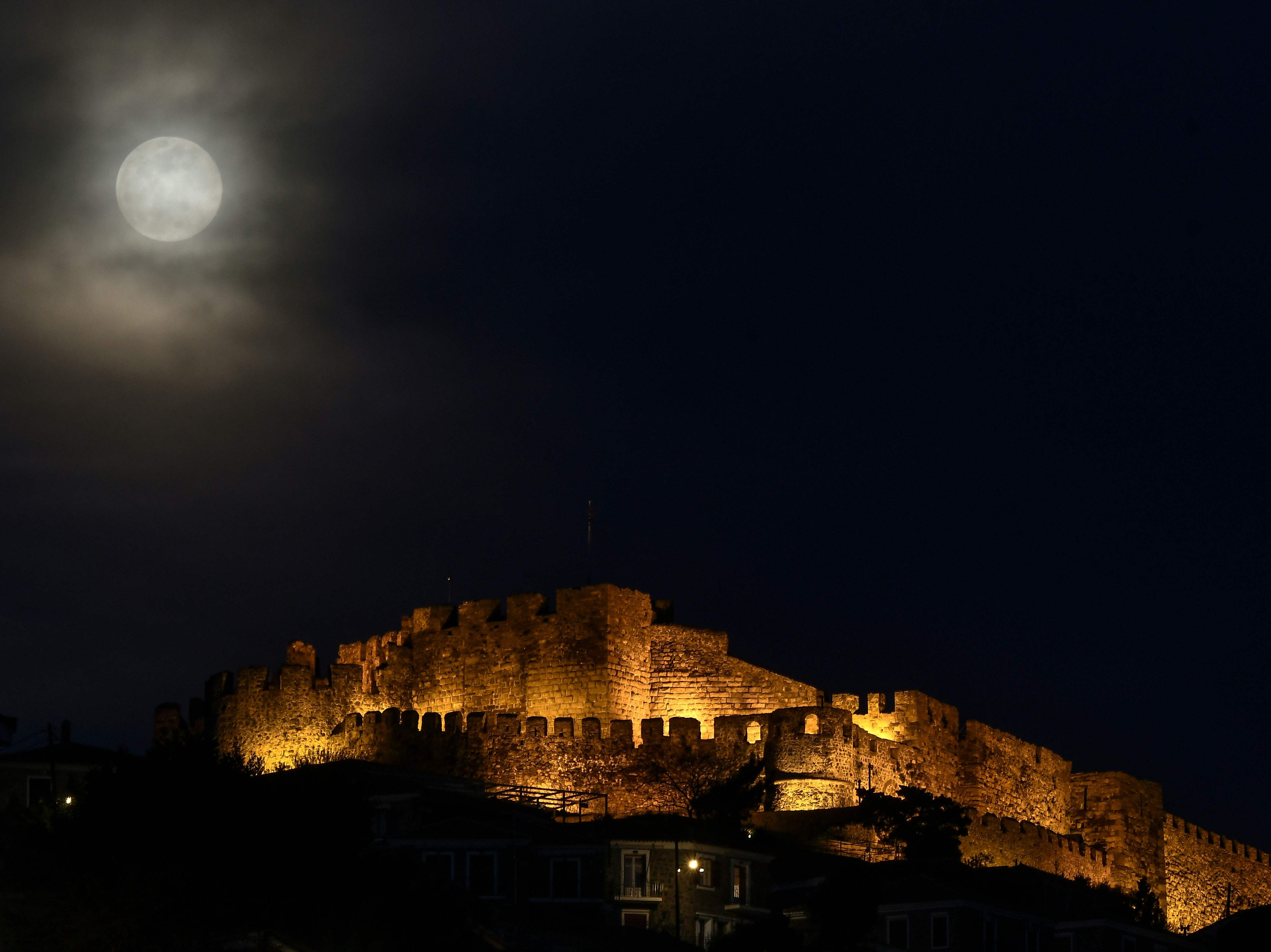A full moon rises next to the ancient castle of Mithymna Molyvos on the Greek island of Lesbos on March 20, 2019.