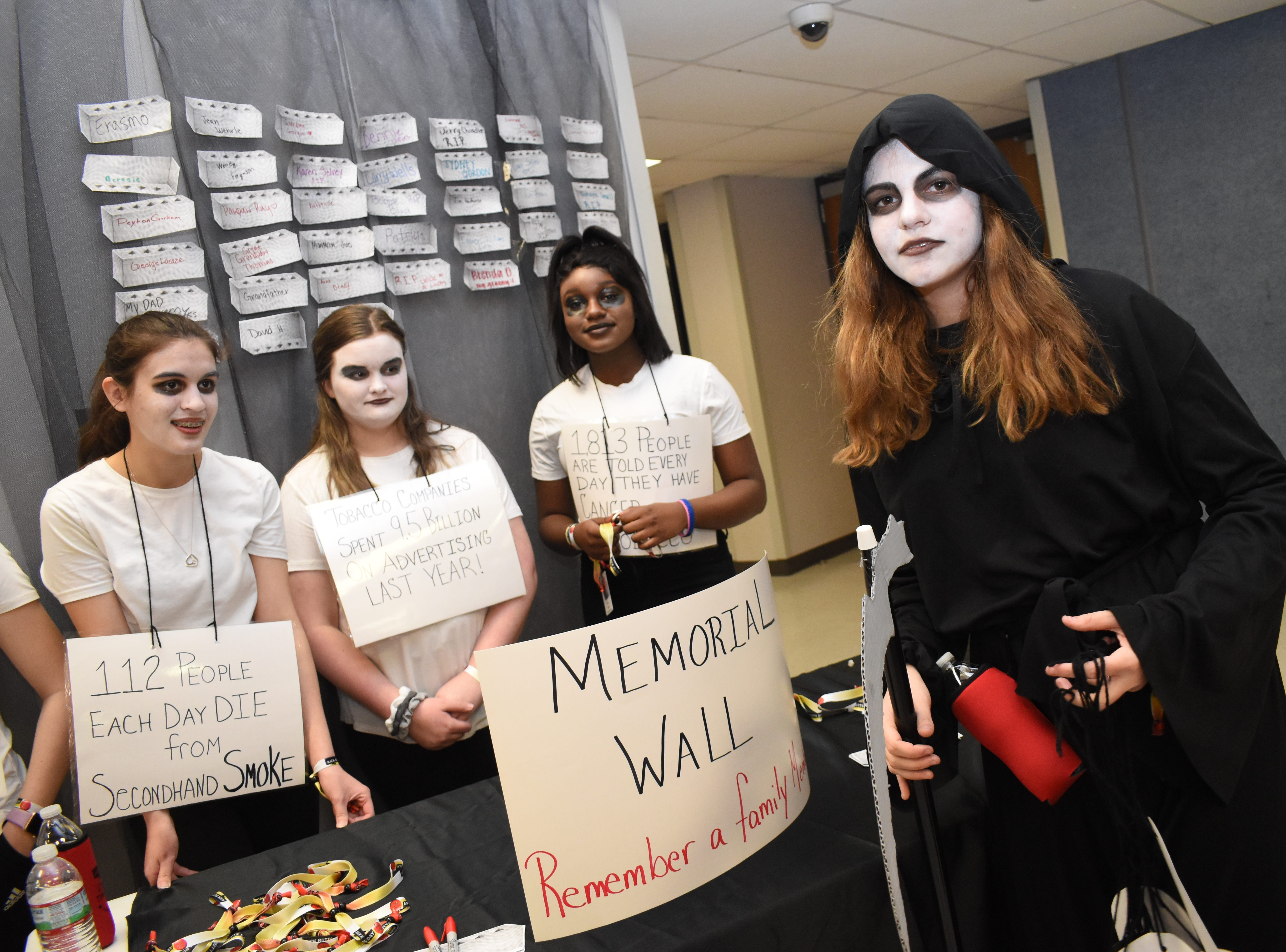 """Kandyce Elliott (far right), dressed as the Grim Reaper as Haley Cohea (back, left). Sydni Walker and Imari Russ wore signs citing information about tobacco use and smoking. All are members of the Living Healthy Club at Tioga High School. The club erected a memorial wall where students could add the name of someone they knew who died from tobacco use. Tioga High School was one of 53 schools in Central Louisiana participating in Kick Butts Day with funding from the Healthy Behaviors School District Partnership Grant from The Rapides Foundation. Kick Butts Day is recognized nationally by young people to raise awareness against the use of tobacco products. A press release from The Rapides Foundation states, """"The Healthy Behaviors School District Partnership Grant seeks to prevent and reduce tobacco use, substance and alcohol abuse, and overweight/obesity by focusing on changing policy, social norms and environments. Grant activities are based on best and promising practices to create comprehensive school- and community-based awareness and prevention programs in order to positively impact Central Louisiana students, educators and staff. The goal is to provide the knowledge and skills necessary to make better and informed behavior decisions leading to healthier lives."""""""