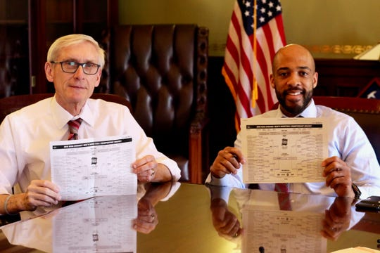 Gov. Tony Evers and Lt. Gov. Mandela Barnes show off their NCAA tournament brackets.