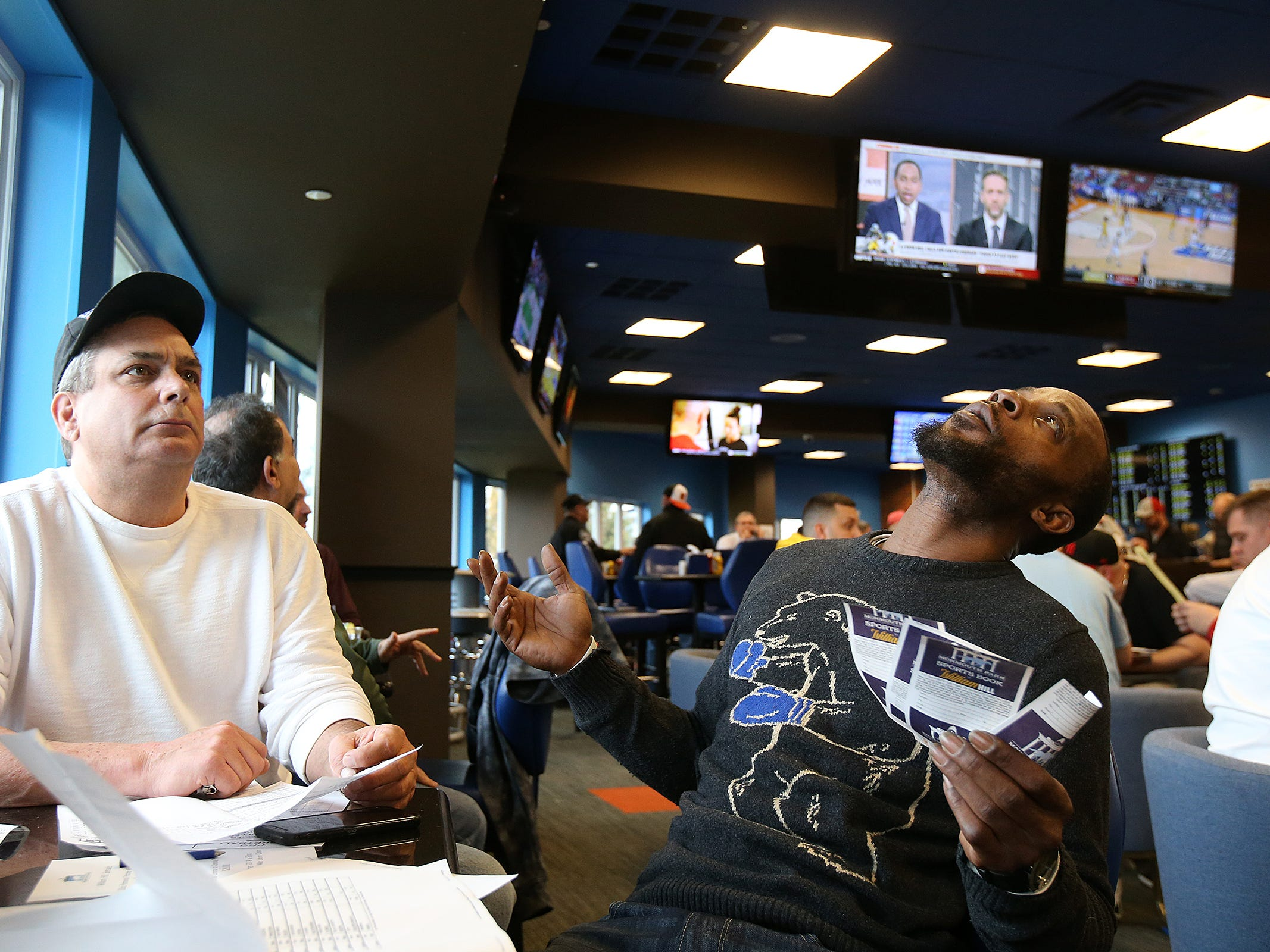 Tim Foley of Colts Neack and Charlie Rogers of Aberbeen, former NFL player, watch the Minnesota vs. Louisville game during March Madness, the NCAA men's college basketball tournament, at Monmouth Park's William Hill Race and Sports Bar in Oceanport, NJ Thursday March 21, 2019.