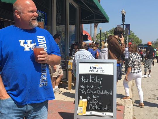 A Kentucky basketball fans drinks a morning cocktail outside of Veterans Memorial Arena in Jacksonville.