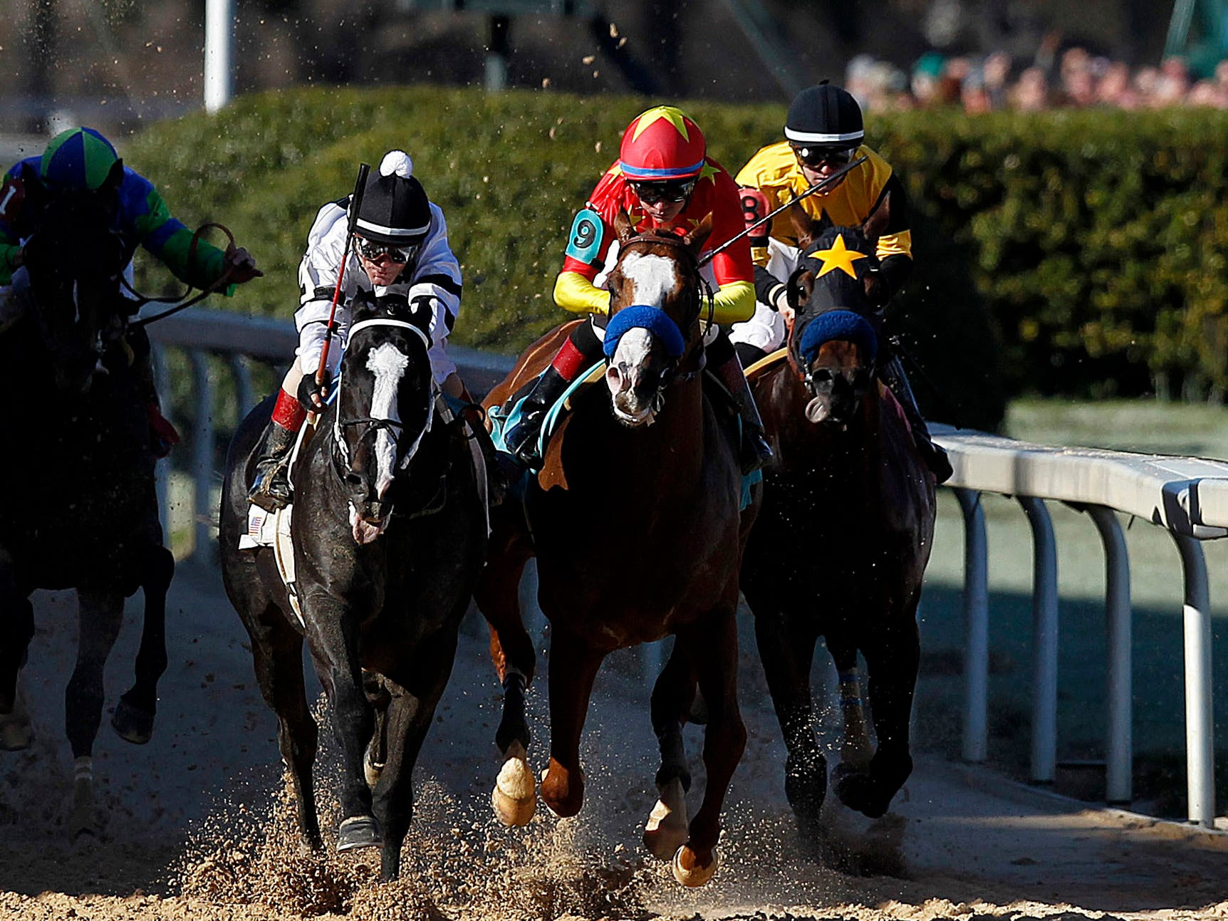 Jockey Jon Court on Long Range Toddy, center, races ahead to beat Improbable ridden by jockey Drayden Van Dyke (9) and Galilean ridden by jockey Flavien Prat (8), to win the first division of the Rebel Stakes  horse race, Saturday, March 16, 2019, at Oaklawn Park in Hot Springs, Ark.