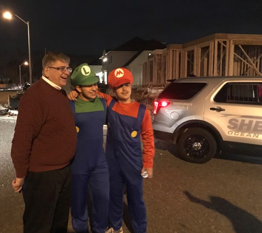 Ocean County Sheriff Michael G. Mastronardy poses for a photo with costumed revelers while on special patrol in Lakewood on the first night of Purim on Wednesday, March 20, 2019.