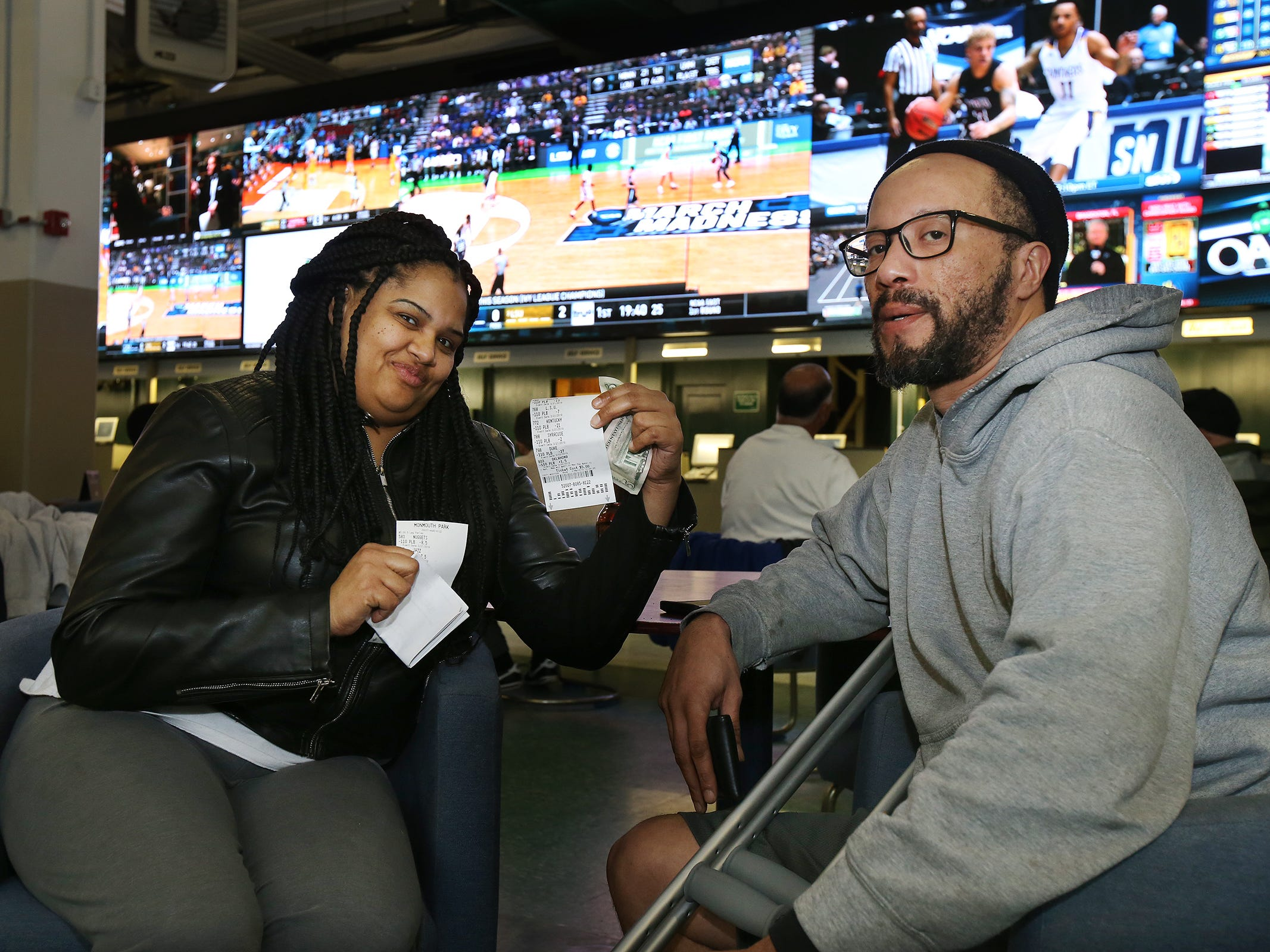 Malika and A.J. Carey of Neptune display their betting slips during March Madness, the NCAA men's college basketball tournament, at Monmouth Park's William Hill Sports Book in Oceanport, NJ Thursday March 21, 2019.