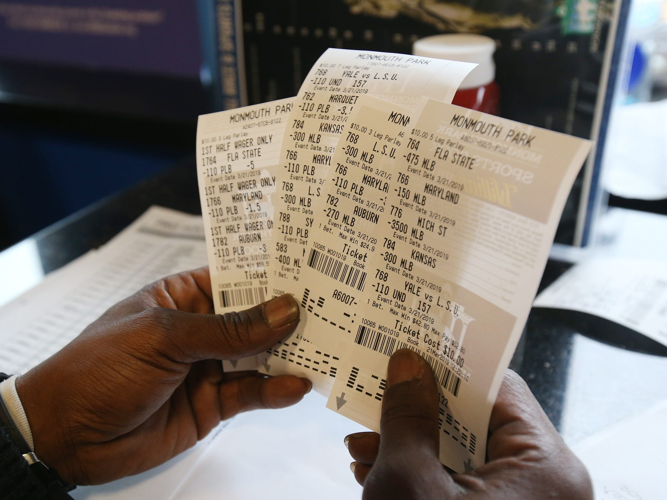 Charlie Rogers of Aberbeen, a former NFL player, displays his betting slips during March Madness, the NCAA men's college basketball tournament, at Monmouth Park's William Hill Race and Sports Bar in Oceanport, NJ Thursday March 21, 2019.