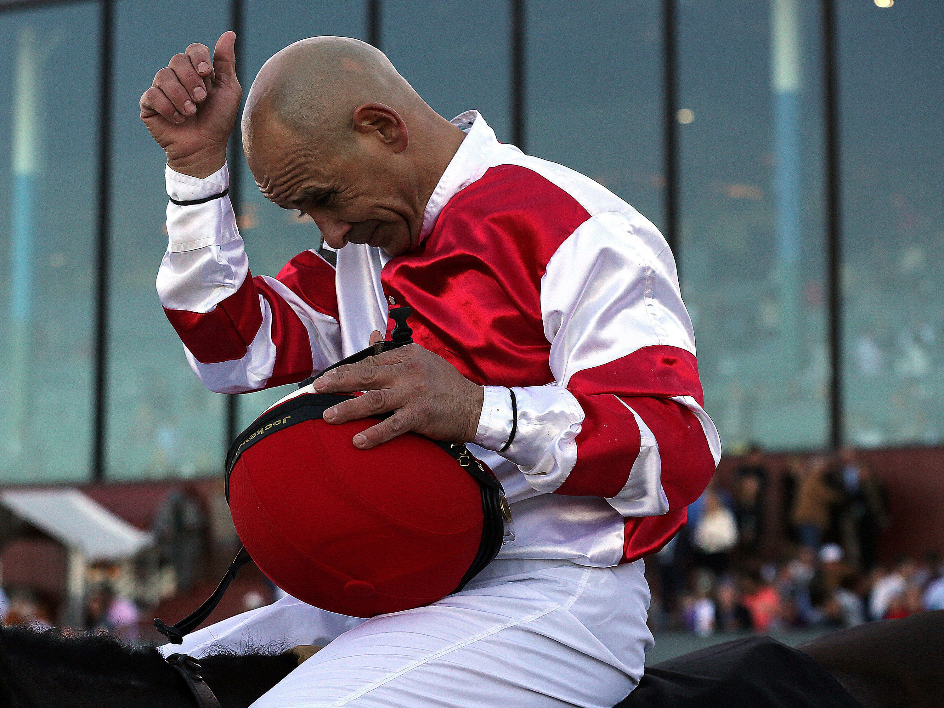 Jockey Mike Smith says a prayer after riding Omaha Beach to win the second division of the Rebel Stakes  horse race, Saturday, March 16, 2019, at Oaklawn Park in Hot Springs, Ark.