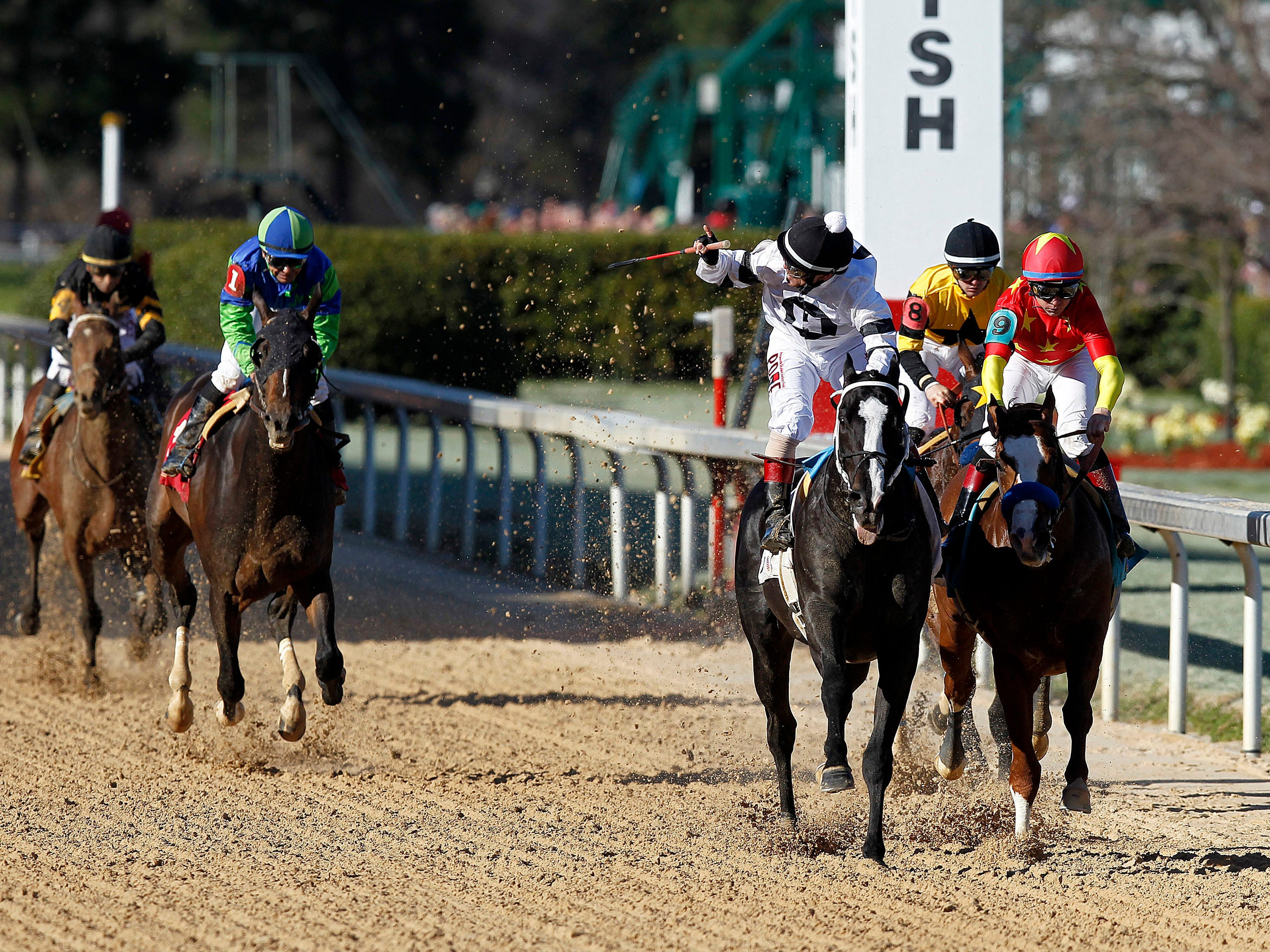 Jockey Jon Court celebrates after Long Range Toddy beat Improbable ridden by jockey Drayden Van Dyke (9) and Galilean ridden by jockey Flavien Prat (8) to win the first division of the Rebel Stakes horse race, Saturday, March 16, 2019, at Oaklawn Park in Hot Springs, Ark.