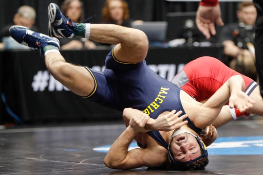 Michigan's Malik Amine, left, gets turned over by Rutgers' Anthony Ashnault in their 149 pound match in the first round of the NCAA wrestling championship, Thursday, March 21, 2019, in Pittsburgh.