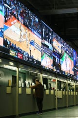 A man makes his bet during March Madness, the NCAA men's college basketball tournament, at Monmouth Park's William Hill Sports Book in Oceanport, NJ Thursday March 21, 2019.