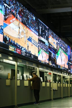 A man makes his bet during March Madness, the NCAA men's college basketball tournament, at Monmouth Park's William Hill Sports Book in Oceanport, New Jersey.