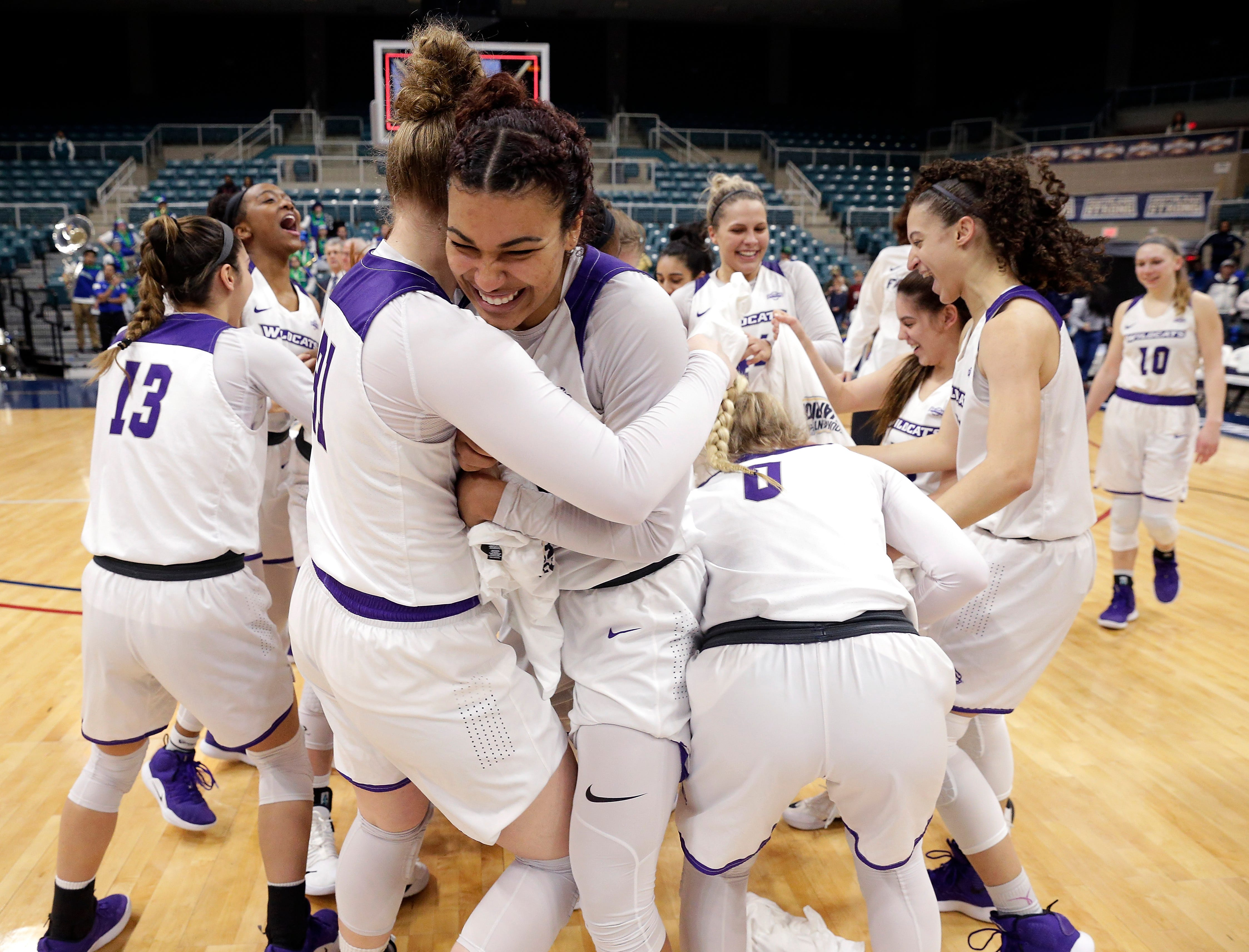 Abilene Christian guard Jazz Taylor and forward Makayla Mabry (foreground) hug as the rest of the team rush center court after defeating Texas A&M-Corpus Christi 69-68 or the Southland Conference women's tournament title Sunday, March 17, 2019, in Katy.