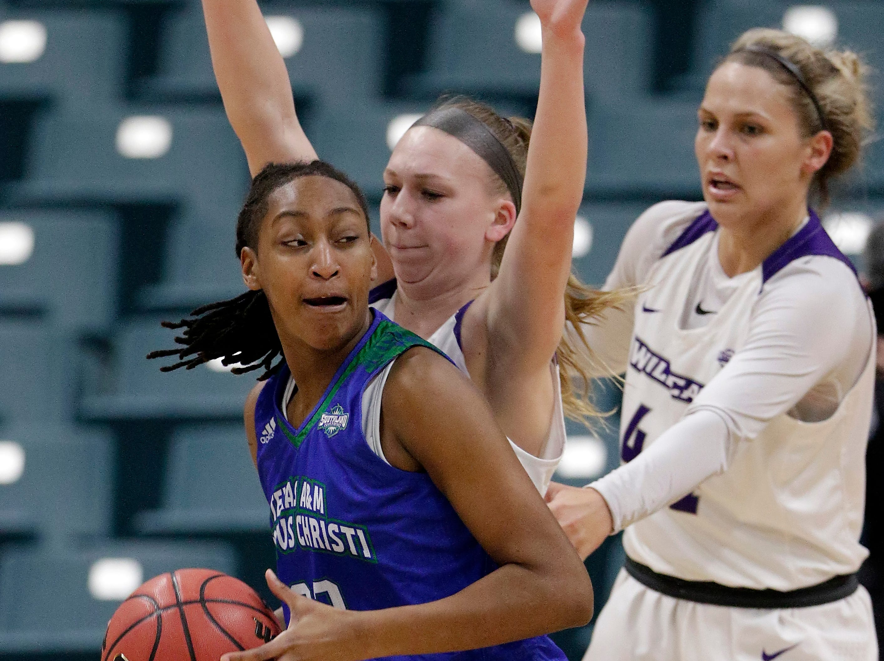 Texas A&M-Corpus Christi guard Dalesia Booth, left, turns to the basket in front of Abilene Christian guard Breanna Wright, middle, and forward Lexie Ducat, right, during the first half of the Southland Conference women's tournament title Sunday, March 17, 2019, in Katy.