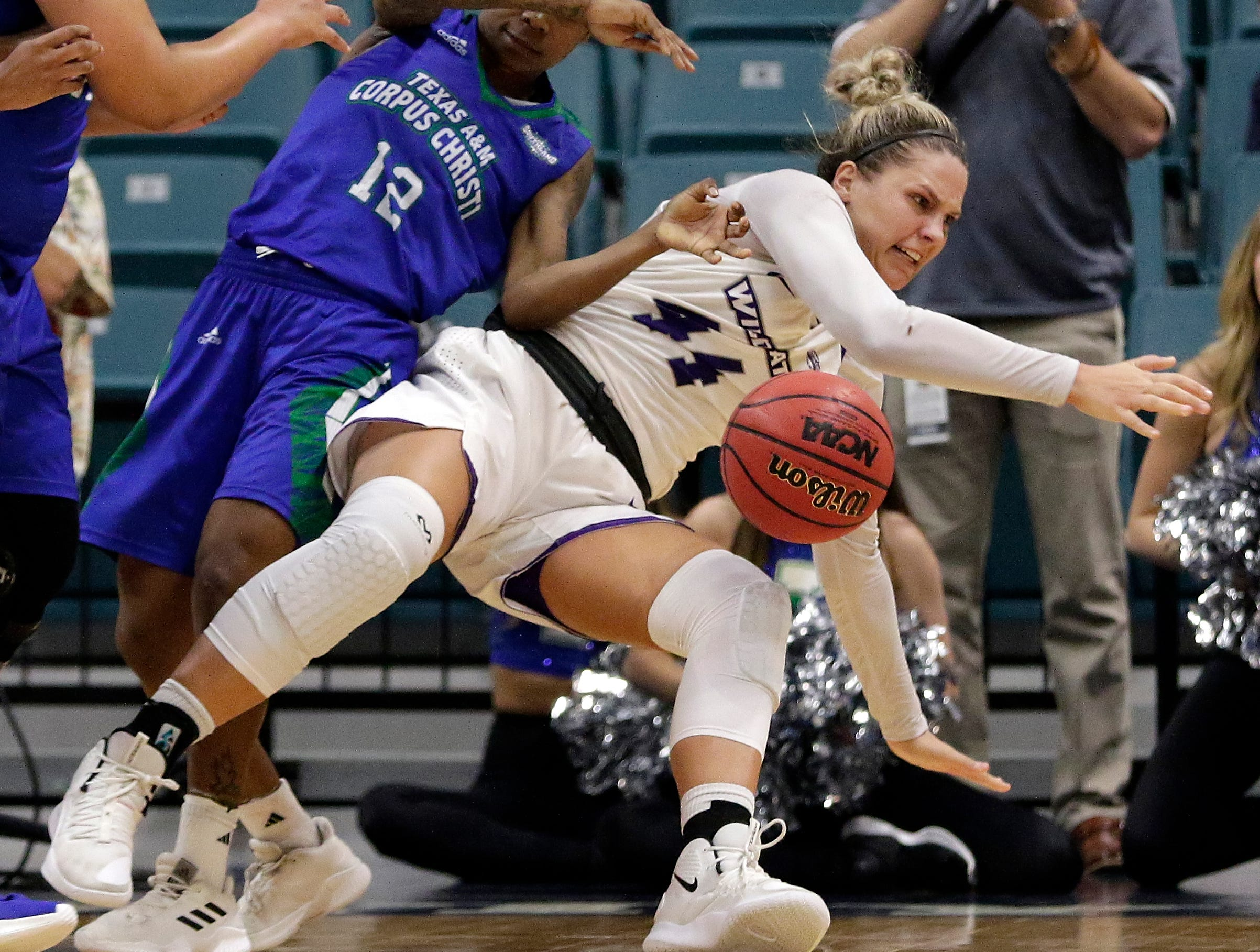 Abilene Christian forward Lexie Ducat (44) falls as she tries to keep the ball from the steal attempt by Texas A&M-Corpus Christi guard Dae Dae Evans (12) during the second half of the Southland Conference women's tournament title Sunday, March 17, 2019, in Katy.
