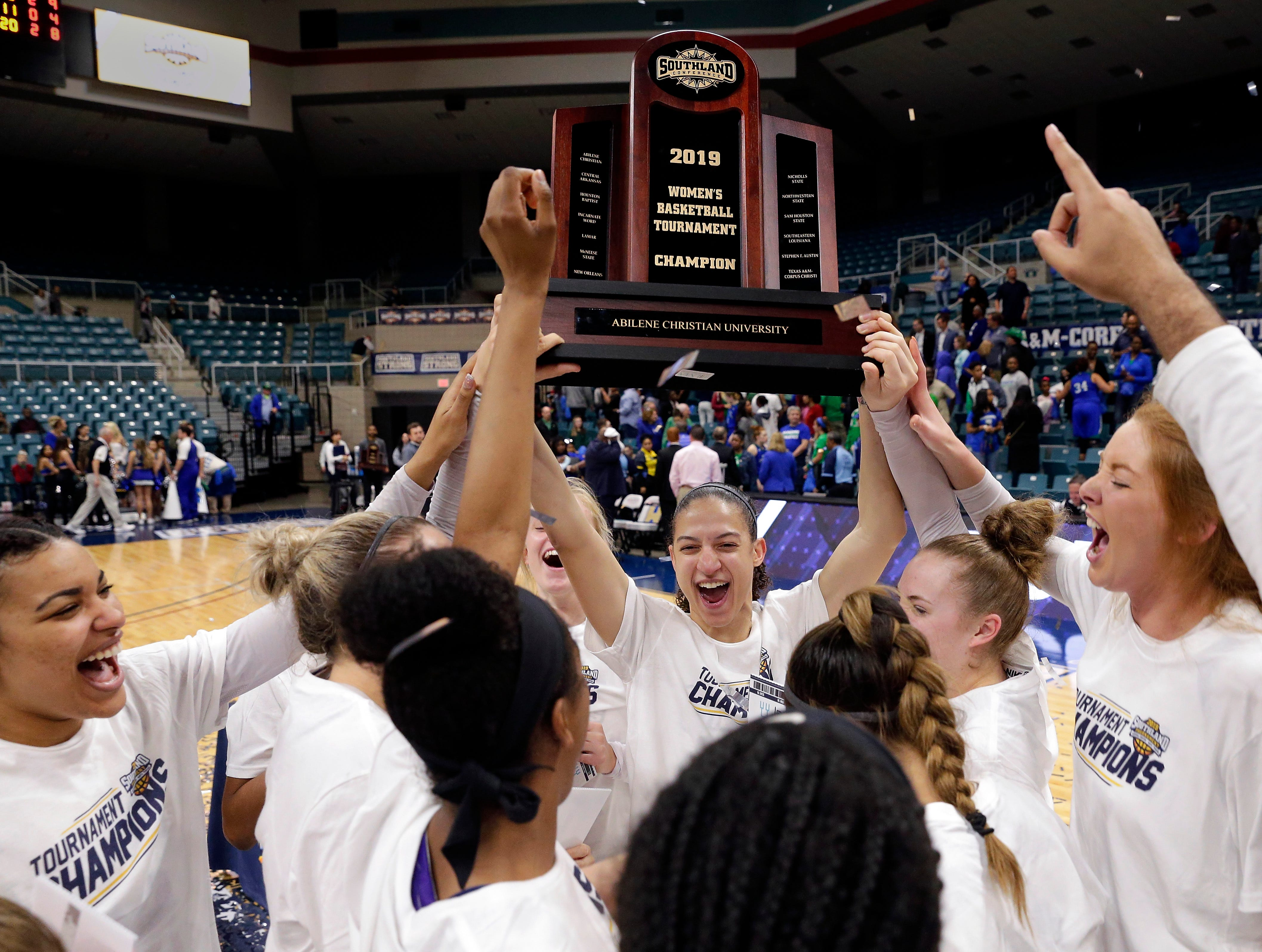Abilene Christian players hoist the conference championship trophy after defeating Texas A&M-Corpus Christi 69-68 for the Southland Conference women's tournament title Sunday, March 17, 2019, in Katy.