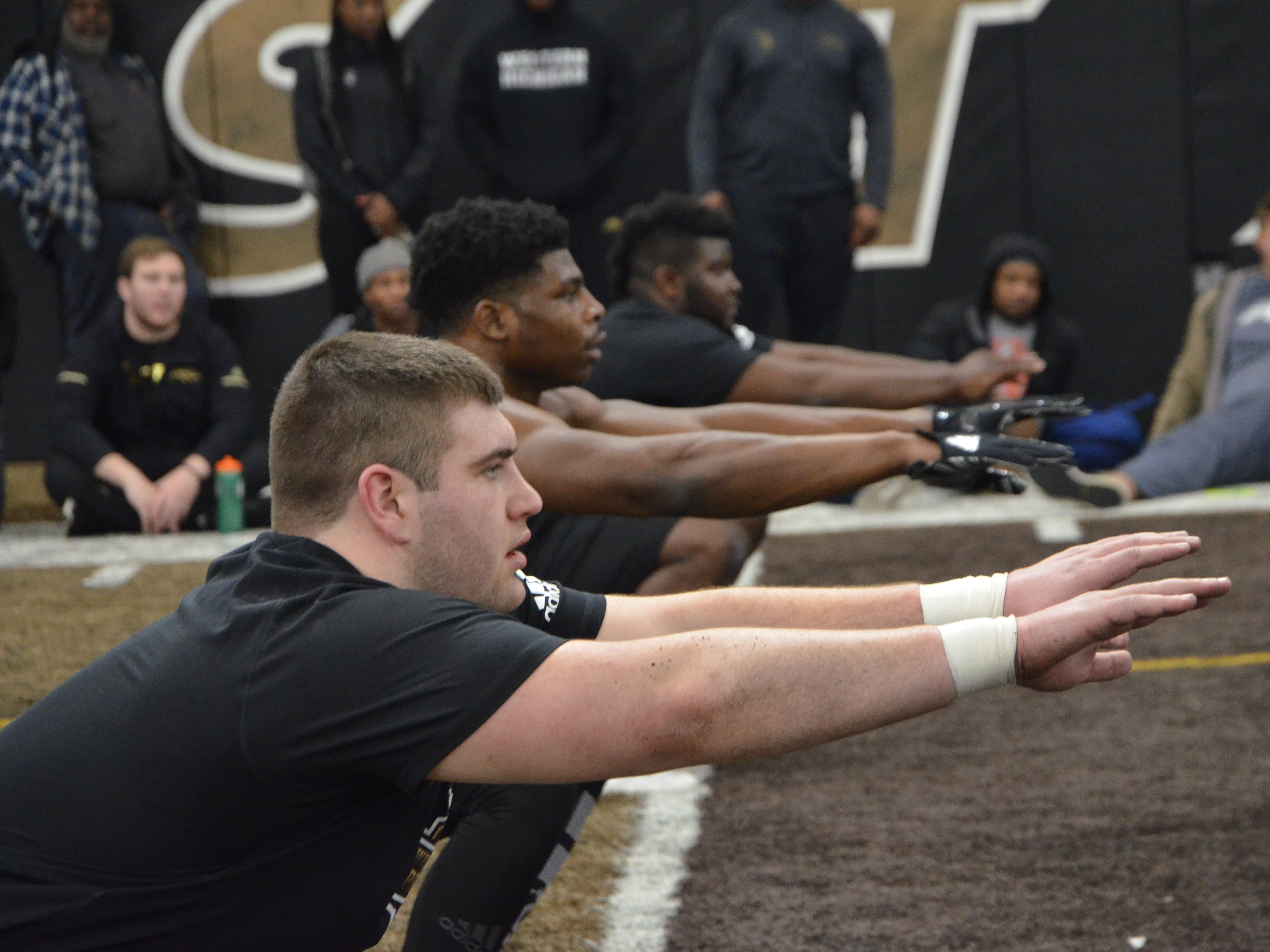 Western Michigan football players John Keenoy, Eric Assoua and Odell Miller perform a drill in front of NFL scouts at the Broncos' Pro Day on Thursday, March 21, 2019.