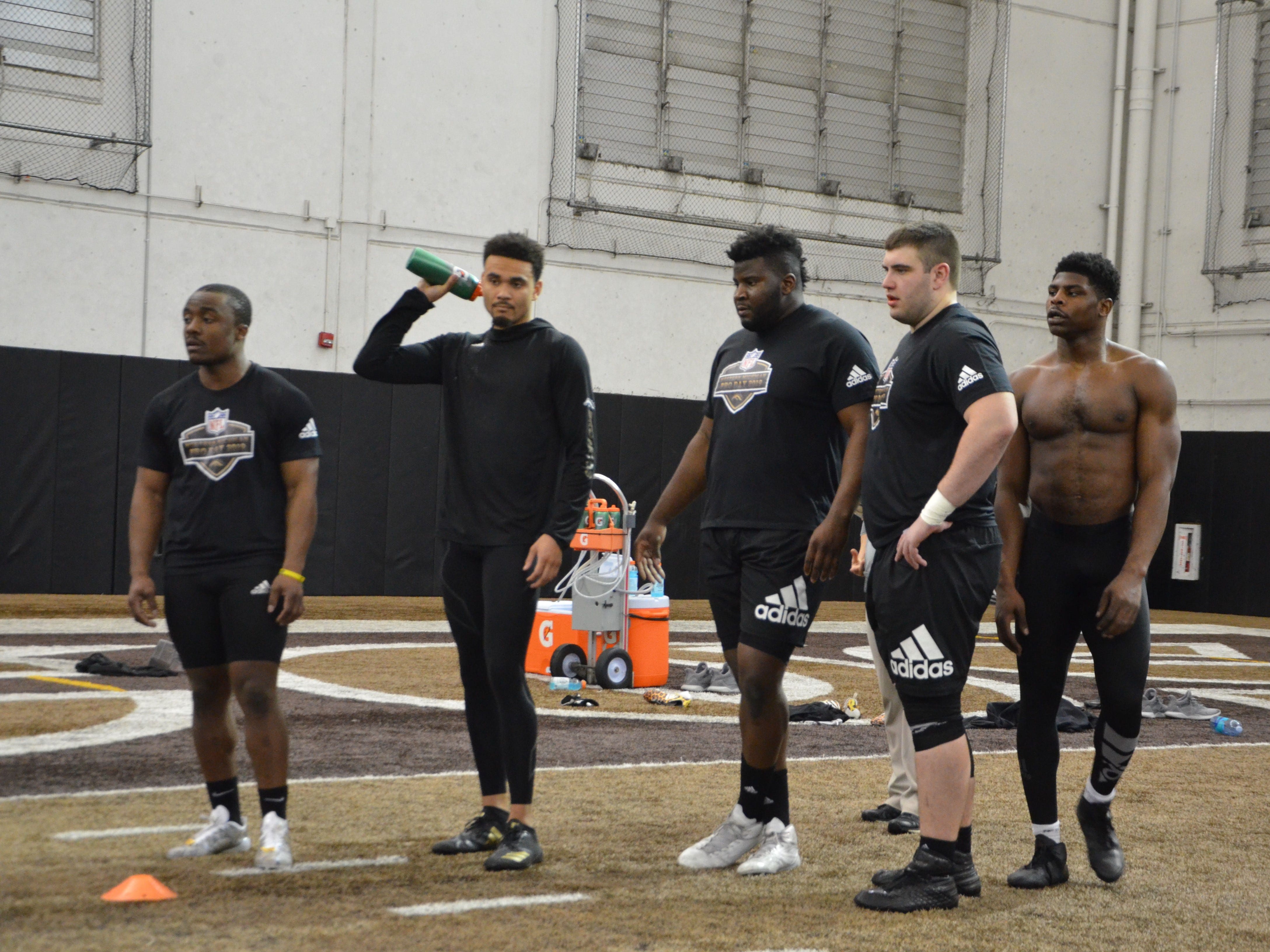 Western Michigan football players (L-R) Jamauri Bogan, Drake Harris, Odell Miller, John Keenoy and Eric Assoua listen for instructions on a drill in front of NFL scouts at the Broncos' Pro Day on Thursday, March 21, 2019.