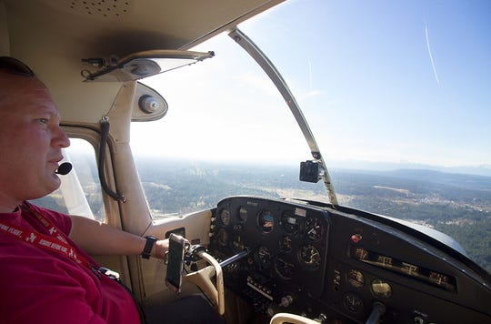 Jason Alferness, looks out of the cockpit of his Cessna 172 during his commute home on Tuesday.