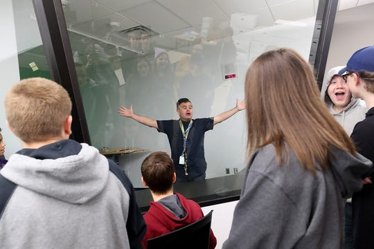 Teacher Michael Brenner gives a shout as he demonstrates the soundproof room — which resembles an aviation control tower — that he and students will use for his aviation classes at the new Central Kitsap Middle School.
