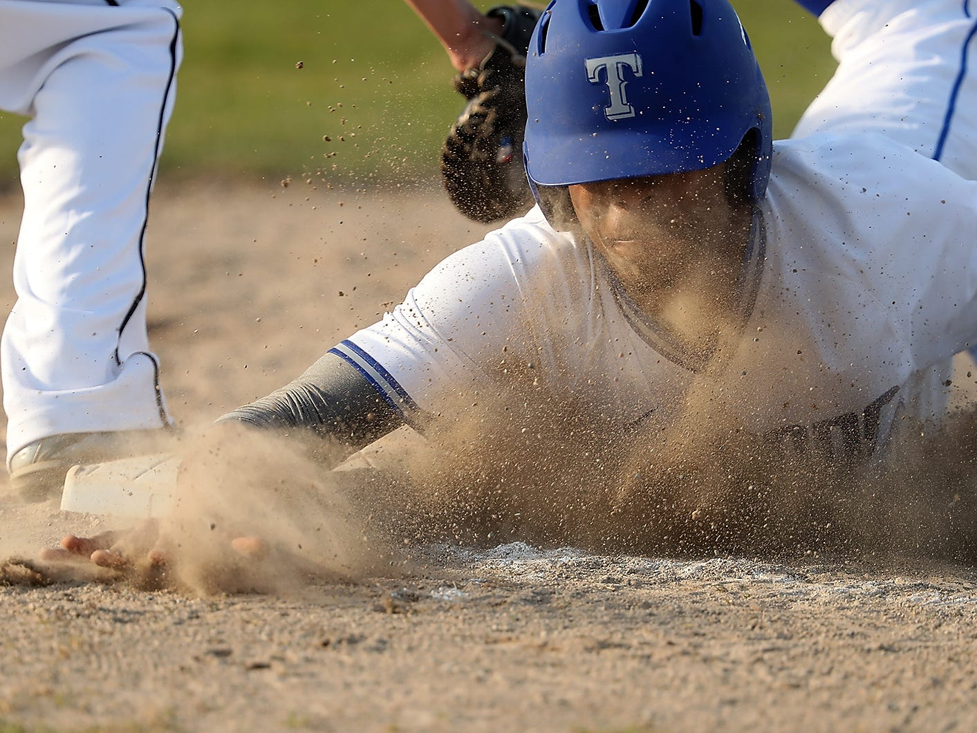 The dirt flies as Olympic's Darelle White dives safely back to first base against Kingston on Wednesday, March 20, 2019.