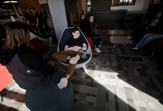 Seventh-grader Layden Walsh, 13, jokingly puts his foot up on an ottoman as he and fellow students check out the library seating areas at the new Central Kitsap Middle School. Students got a tour of the completed building ahead of the district's spring break. They will start attending classes there after spring break.