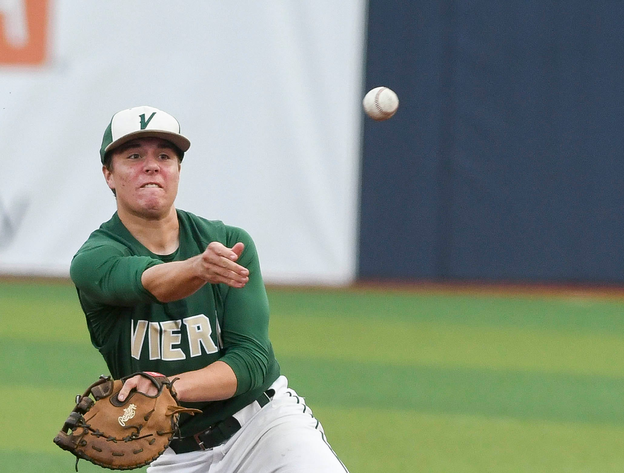Viera's Brady Janssen throws out a baserunner from his knees during Wednesday's game against Sebastian River at USSSA Space Coast Stadium.