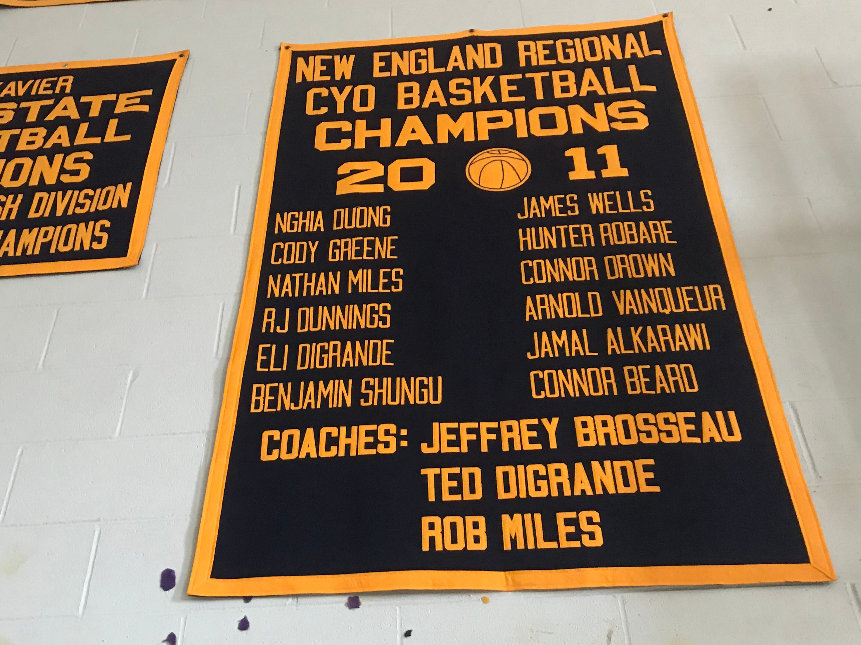 Benjamin Shungu's name, bottom left, is seen on a banner at St. Francis Xavier School in Winooski on March 21, 2019.