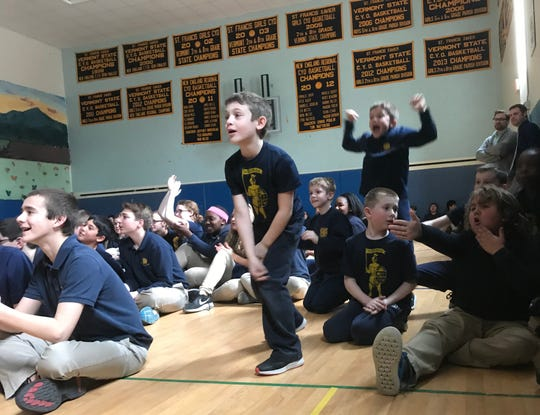 Second-grader Kellan O'Brien, center, joins classmates at St. Francis Xavier School in Winooski while watching a March Madness game featuring the UVM Catamounts on March 21, 2019.