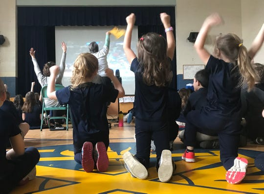 Students at St. Francis Xavier School in Winooski cheer the UVM Catamounts basketball team on March 21, 2019.