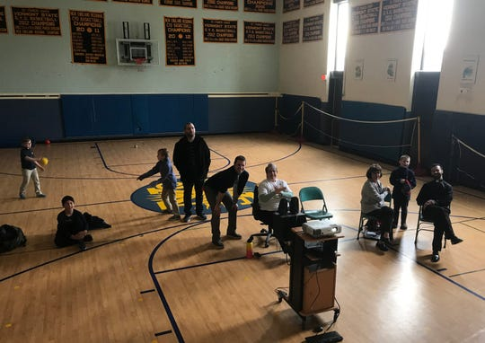 Faculty, staff and a few students at St. Francis Xavier School in Winooski linger in the gym to watch a livestream of the UVM Catamounts game after classes let out March 21, 2019.