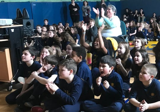 Fourth-grade teacher Diane Dufresne, seated, joins students at St. Francis Xavier School in Winooski in cheering on the UVM Catamounts on March 21, 2019.