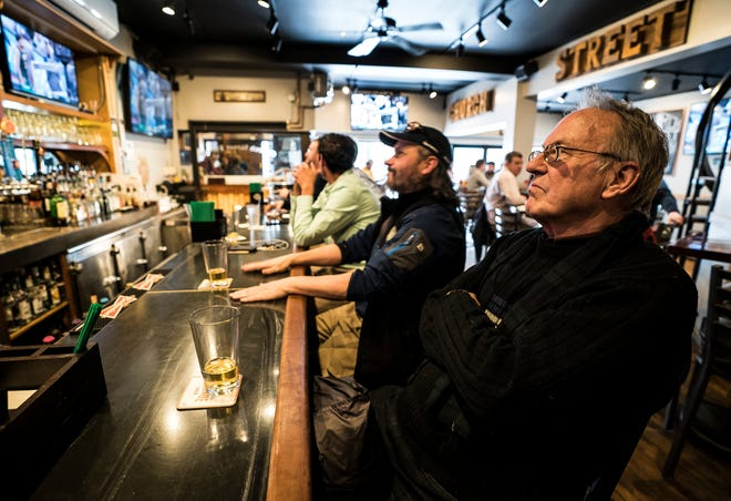 Richard Cowperthwait of St. Albans sits back in his chair, arms folded, after watching the UVM men's baseball team fall to Florida State in the first round of the NCAA tournament. Dozens packed the Church Street Tavern in Burlington on Thursday, March 21, 2019, to watch the game.