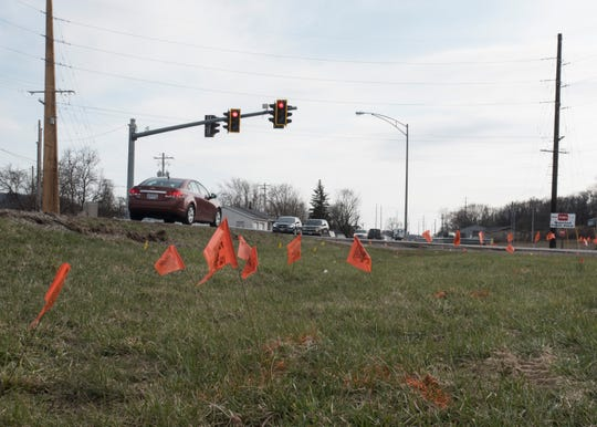 Large orange utility flags were placed by the local utility company, which had lines to move in preparation for the turn-lane addition and intersection improvement project here.