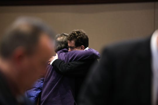 Tracey Abraham embraces with a man in the crowd after the first day of his hearing on Thursday March 21, 2019.
