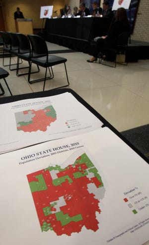 FILE-  In this Aug. 23, 2011 file photo, maps showing Ohio State house and senate districts lie on a table during a hearing of the The Ohio Apportionment Board, in Cleveland.