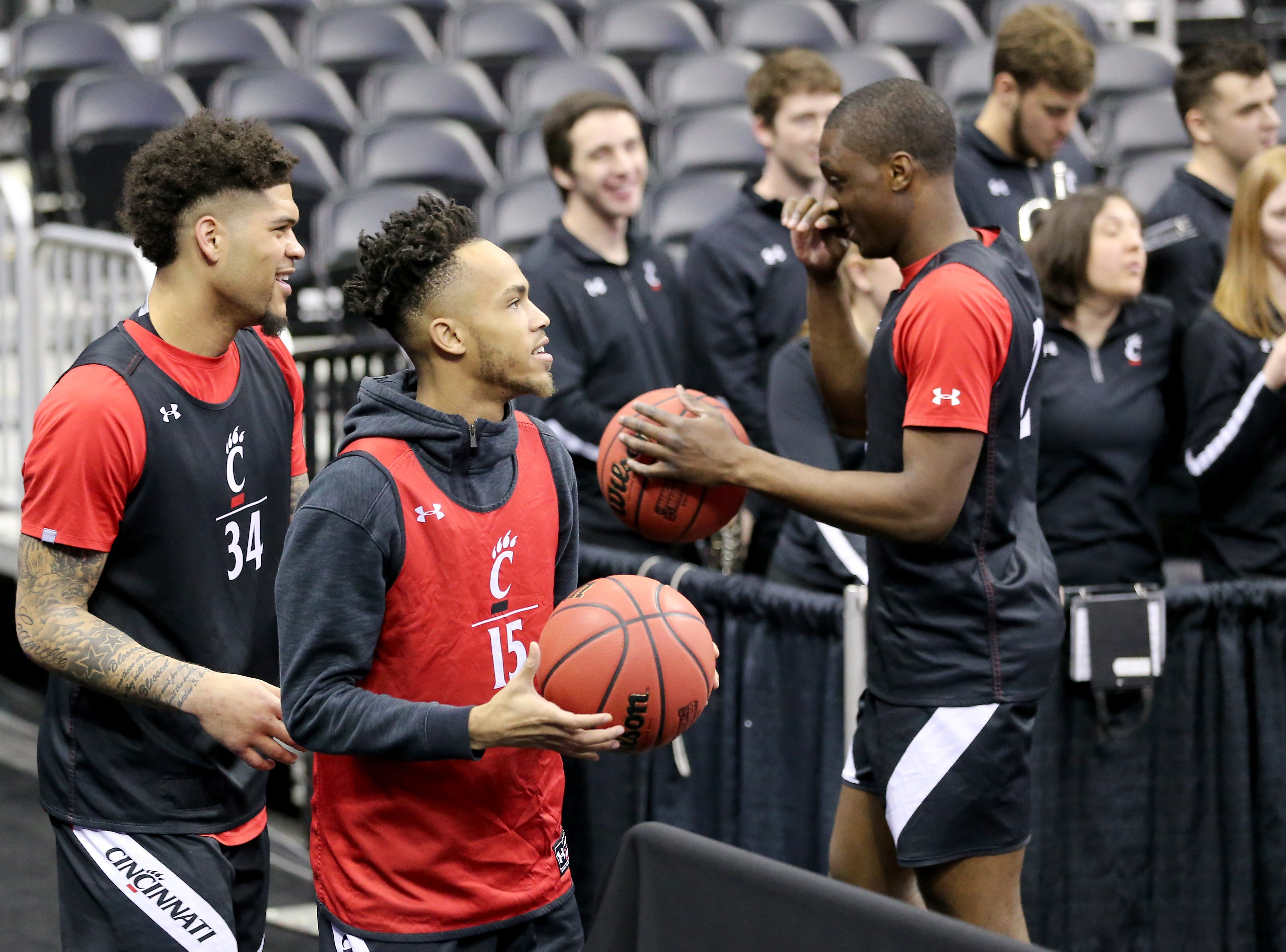 Cincinnati Bearcats guard Jarron Cumberland (34), guard Cane Broome (15) and guard Keith Williams (2) take turns taking shots from the corner during open practice, Thursday, March 21, 2019, at Nationwide Arena in Columbus, Ohio.