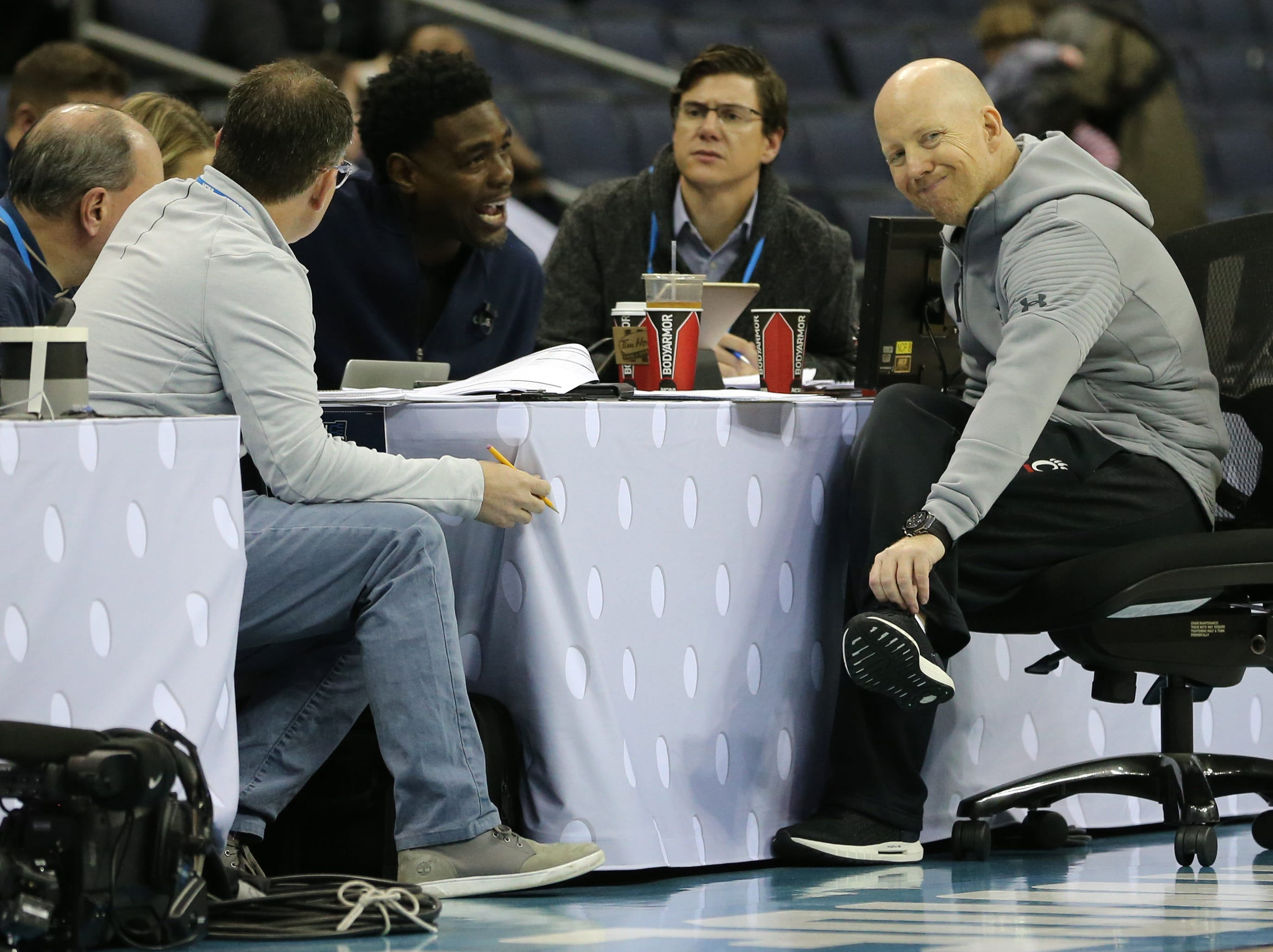 Cincinnati Bearcats head coach Mick Cronin speaks with the broadcast team, including Chris Webber, center, during open practice, Thursday, March 21, 2019, at Nationwide Arena in Columbus, Ohio.